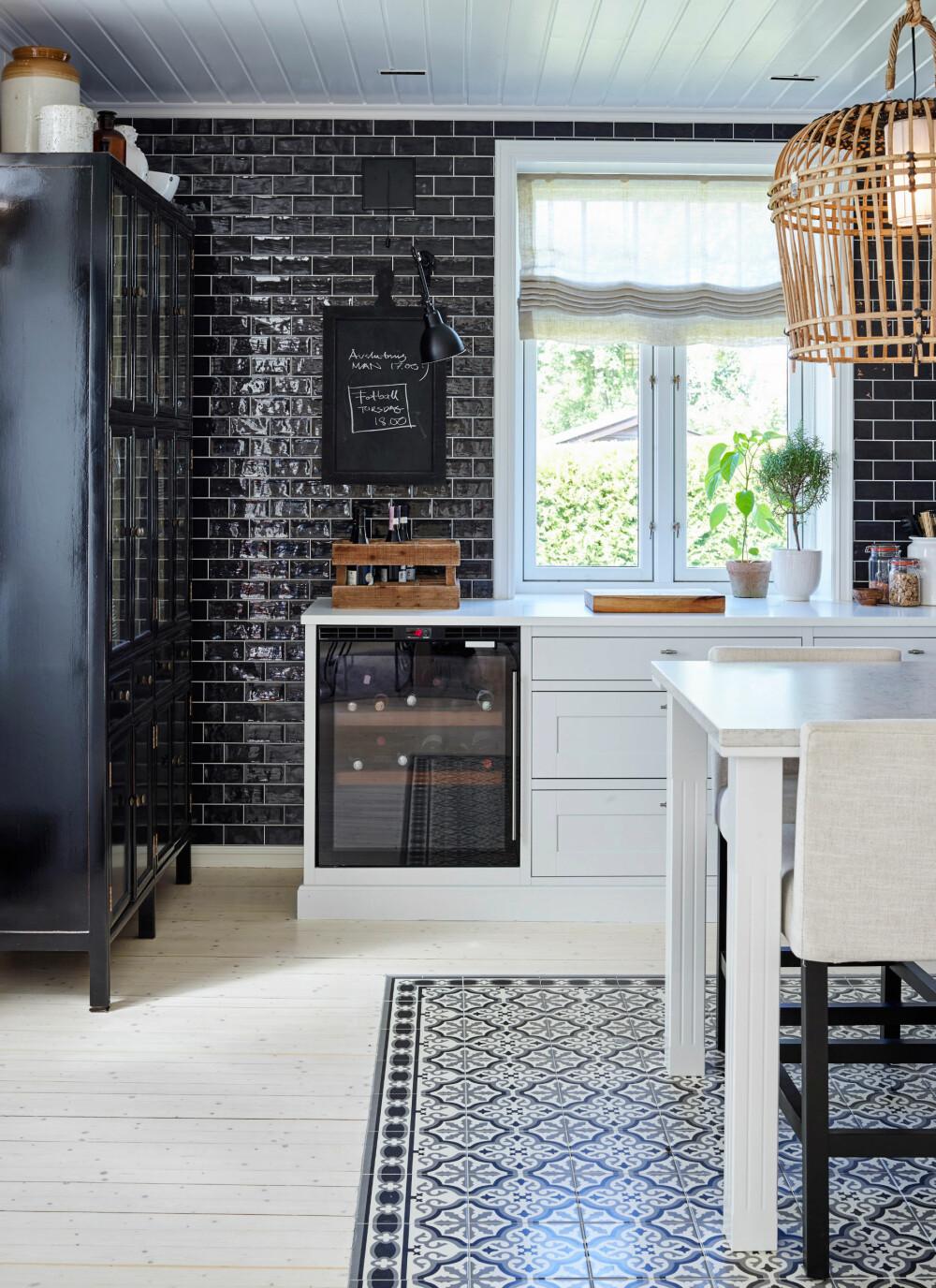FLISLAGTE VEGGER: Alle veggene er flislagt med glaserte fliser fra L-Flis og Interiør. Det svarte skapet i hjørnet har glassdører og bryter med de integrerte hvitevarene.