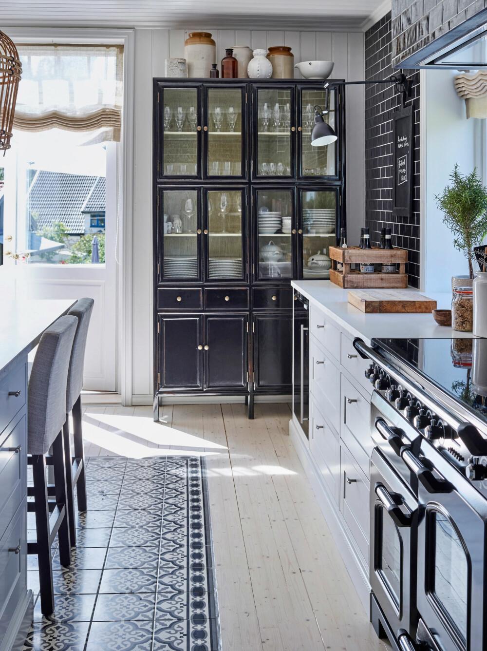 FLISER OG TRE: Det svarte skapet fra House Doctor rommer servise og andre ting som er i bruk daglig. Herregårdskjøkkenet er fra Sigdal Kjøkken, og det originale gulvet i tre har brede planker.