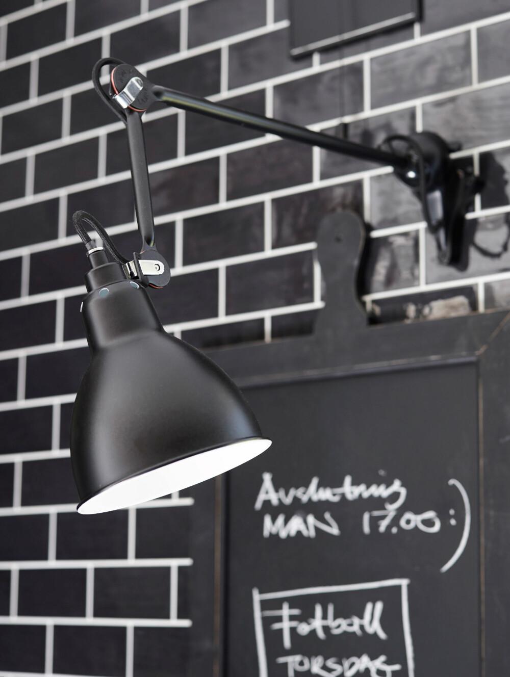 HÅNDLAGDE FLISER: Flisene på veggen er håndlagde, og alle er derfor ikke helt like. Den svarte lampen gir arbeidslys ned på benken, den har bevegelig arm slik at lysstrålen kan varieres. Tenk alternativt når det kommer til belysning!