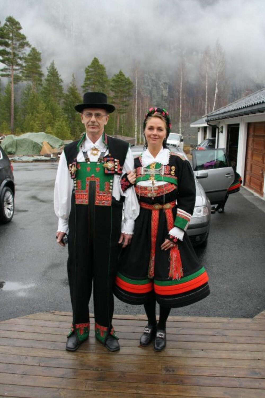 BUNAD:  Hva slags bunad er dette?: Setesdalsbunad.  Hvem ser vi på bildet? : Alfred Rysstad og Karen Synnøve Rysstad  Hvor er bildet tatt, og i hvilken situasjon?: Dåpen til Karen Marie.