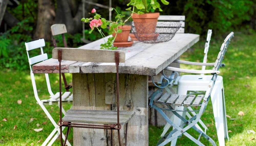 Et italiensk langbord lagd av gammelt trevirke, er plassert under et tre i hagen. Bruk gjerne forskjellige stoler rundt bordet, det skaper en rustikk stemning.