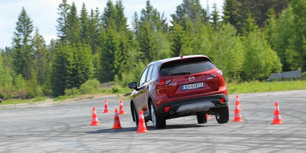 INGEN DRAMATIKK: Selv om den løfter på bakhjulet i unnamanøver, er Mazda CX-5 en av de snilleste og mest velkjørende modellene i SUV-klassen.