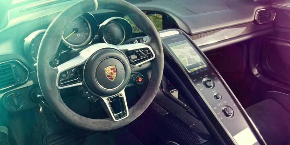 INNE I 918: KOMMANDOHJUL: Riflet aluminium er et tema i cockpiten til 918. De gir deg tilgang til ulike skjermmenyer. PEKESKJERM: Det buede glasspanelet har full multitouch-funksjonalitet, og styrer også den andre skjermen. KJØREMODUS-KNAPP: Velg mellom Elektrisk, Hybrid, Sport eller Race. Den røde knappen? Hot Lap, som tyner batteriet for alt. KNAPPEPANEL: Tre veldig enkle knapper som styrer (fra toppen) cruise, manuelt gir og konfigurering.
