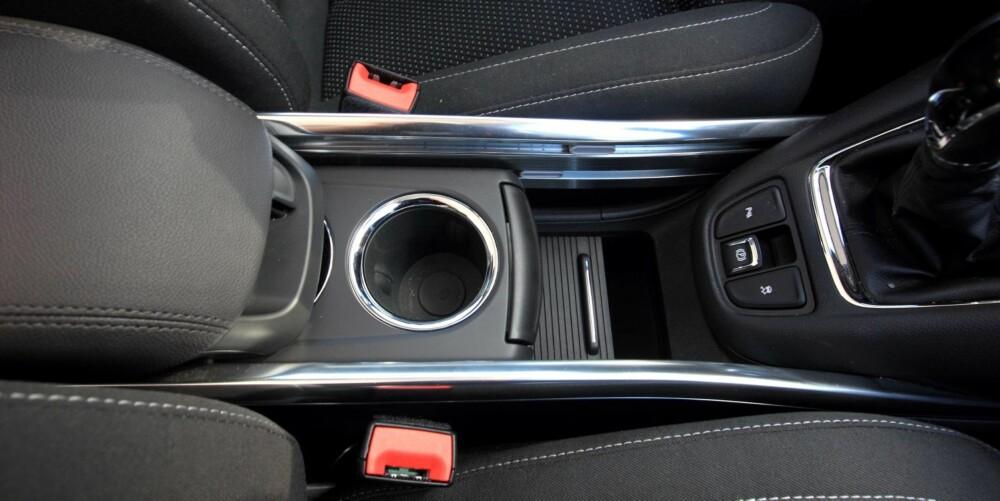 """OPPBEVARING: Som normalen er for flerbruksbiler har Opel Zafira Tourer mange smarte oppbevaringsrom. Mellom forsetene finner man ett eksempel: I tre """"""""etasjer"""""""" kan armlene, koppholdere og en lukkemekanisme skyves fram og tilbake etter behov. FOTO: Egil Nordlien"""