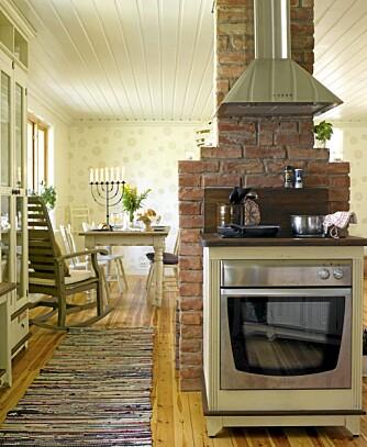 SPESIALLAGET: Når du får kjøkkenet skreddersydd etter dine mål, er det fullt mulig å bestille noe så uvanlig som en frittstående komfyr med innebygd ovn. Her er det i tillegg bestilt en røff veggplate til komfyren, som beskytter veggen mot smuss. Pipa bak komfyren er kledd med gylden murstein. Siden komfyren var bredere enn pipa, ble mursteinen bygget litt ut på begge sider der den skulle stå.