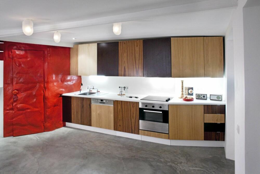 Kjøkkenet i den lille leiligheten har skap som veklser mellom lyst og mørkt treverk. Både oppe og nede. Den brannbilrøde veggen mot badet setter et ekstra piff på innredningen.