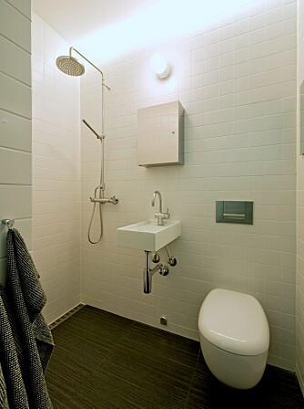 ÅPNER ROMMET: I det lille badet samles alt utstyr på én vegg. Rennesluket fra Unidrain gir ensidig fall og skrå gulvflater, og da kan man også bruke bare slike store, 30 x 60 cm Vitra gulvfliser. En 28 cm bred og 40 cm dyp Boxo vask bygger ut i rommet.