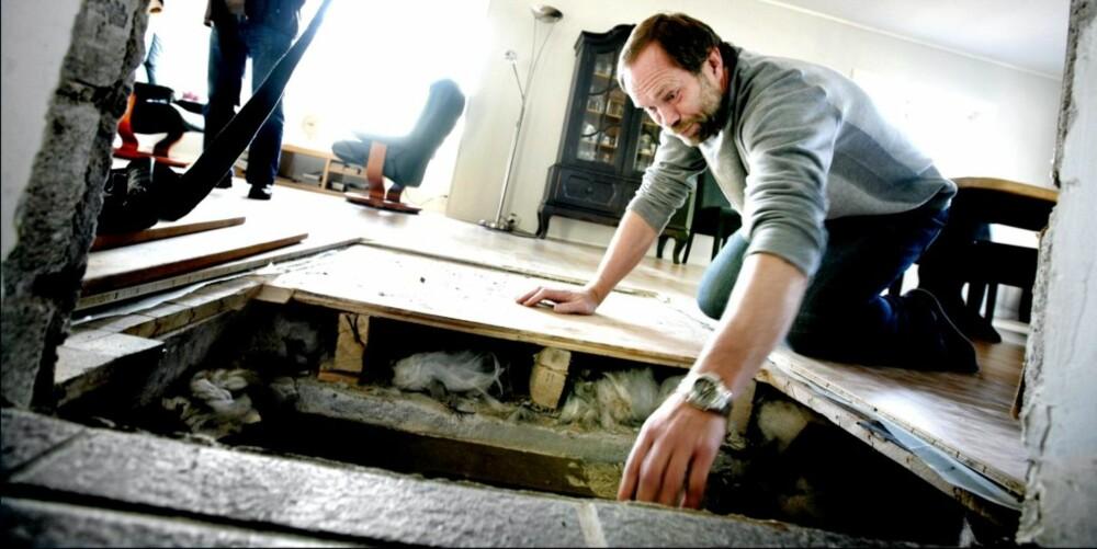 PIPELØPET: Petter Hultin lener seg på området der peisen tidligere sto. Nå blir det god plass i stua, når brennkammeret flytter inn i selve pipa.