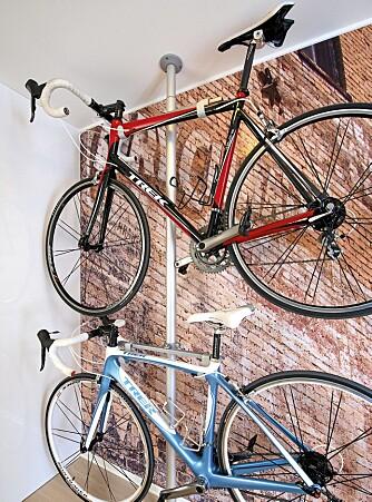 SYKKELSTATIV I entreen henger parets sykler alltid parat. Med «Stolmen» teleskopstang fra Ikea og en tverrstilt stålstang fra Biltema lagde eierne et stødig stativ i to høyder. Fototapetet på bakveggen er fremstilt hos FotoPhono av et murveggmotiv hentet fra parets tur til Colorado.