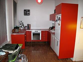 FUNKSJONELT: Den oransje fargen passer til det enkle, retropregede kjøkkenet.