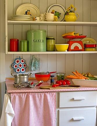 Landlig kjøkken med åpne hyller og stoff foran underskap.