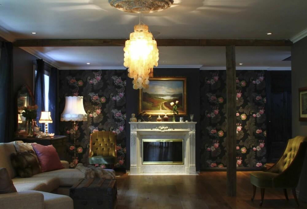 Paret ønsket at stuen skulle være som en hule de kunne trekke seg tilbake i og valgte mørke farger med utganspunkt i tapetet fra Designers Guild.