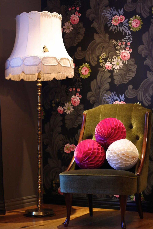 En sommerfugl og rosa pom poms pynter opp på en stol og en lampe i det ene hjørnet av stuen.