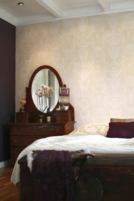 Soverommet har dusgul tapet på den ene veggen og er ellers malt i en mørk aubergine farge. Ved siden av sengen står et vakkert gammelt sminkebord med speil.