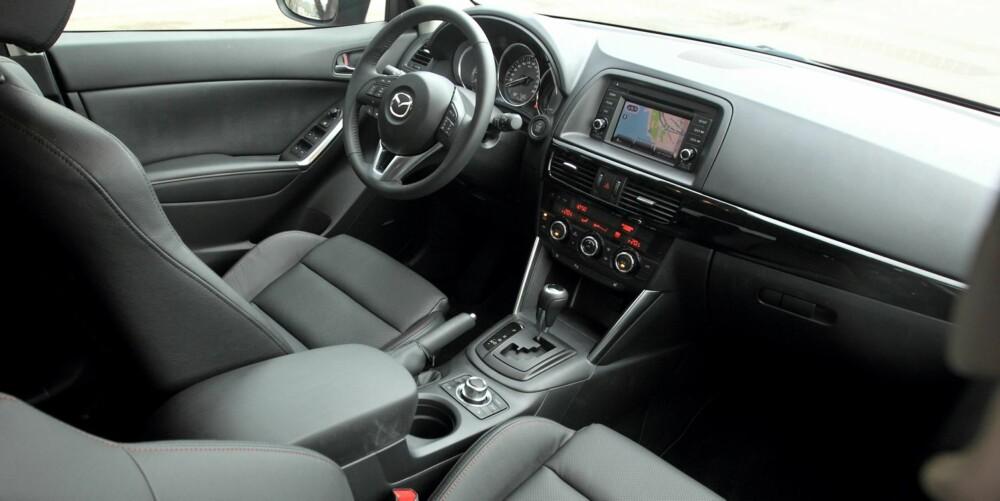 RYDDIG: Mazda CX-5 i Sport-utgave har masse utstyr inkludert skinnseter. Det løfter inntrykket av interiørkvaliteten, uten at bilen når statusbilnivå. (Testbilen har manuelt gir, ikke automatgir som på bildet.) FOTO: Egil Nordlien, HM Foto