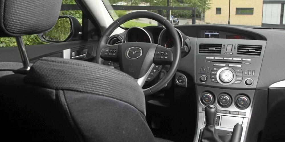 SPORTY: Interiøret i Mazda 3 er småsporty, men preges av en del plast. Særlig påkostet føles den ikke. Sportssetene er imidlertid å anbefale!