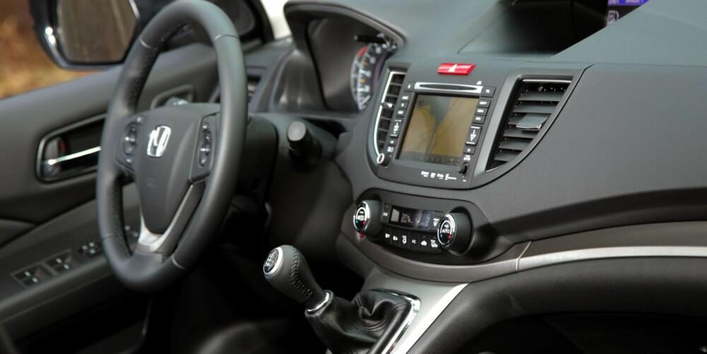 RYDDIG: Innvendig framstår Honda CR-V som ryddig, med fint grupperte instrumenter. Girspaken står akkurat der hånda faller når du slipper rattet. Med tanke på testbilens pris - nesten en halv million kroner - synes vi plastkvaliteten noen steder er litt billig. FOTO: Egil Nordlien, HM Foto