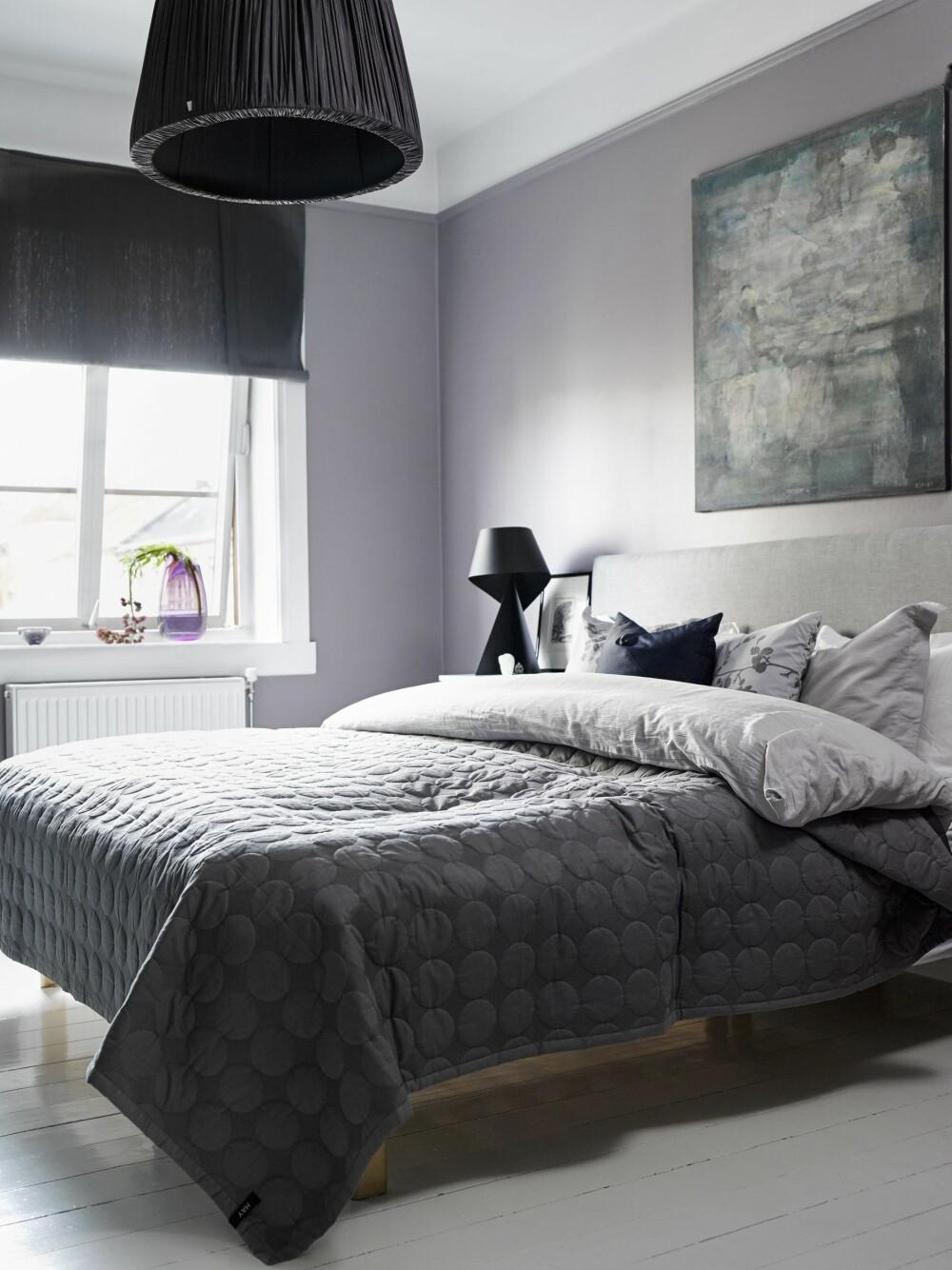 HULESTEMNING: Veggene i soverommet er malt i fargen Lady Lys Aubergine 3206 og bidrar til lun og god stemning. Maleri av Arne Jan Espeland, sengeteppe fra Hay. Den stofftrukkede pendelen er fra Tine K. Home, bordlampe fra Habitat.