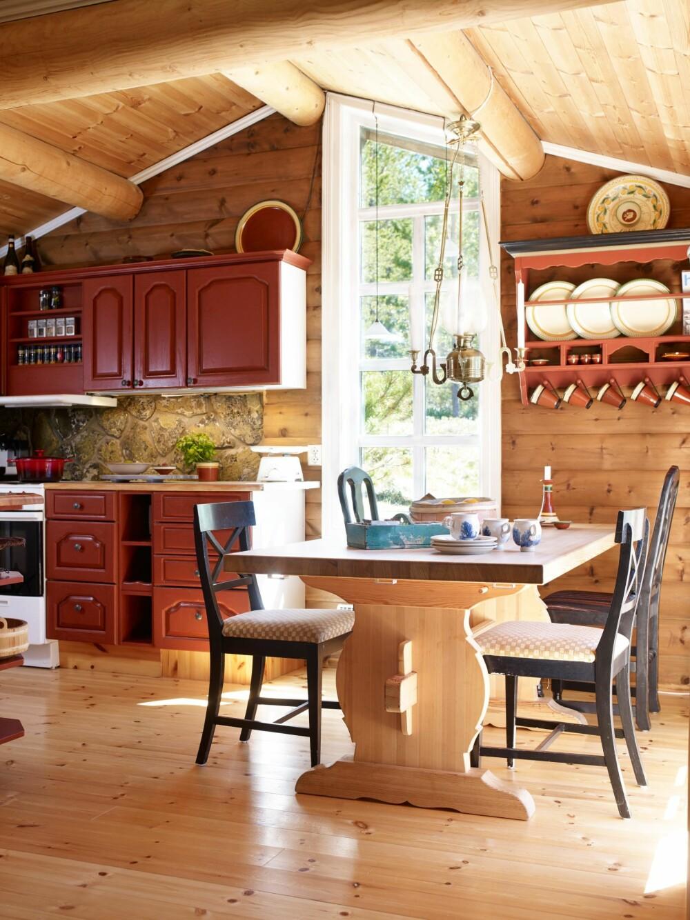 NATUREN TETT PÅ: Tilbygget med kjøkkenet har en lun utsikt mot skogen innenfor. Vinduet går helt ned til gulvet. I hyllene er det keramikk fra Potteriet på Røros.