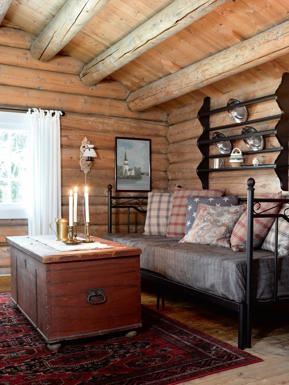 GJESTEHYTTA: Sengen fungerer som sofa på dagtid. Hyllen er laget av Sidsels onkel. Kisten er kjøpt på auksjon. At sengen og hyllen er svart, gir karakter til rommet.