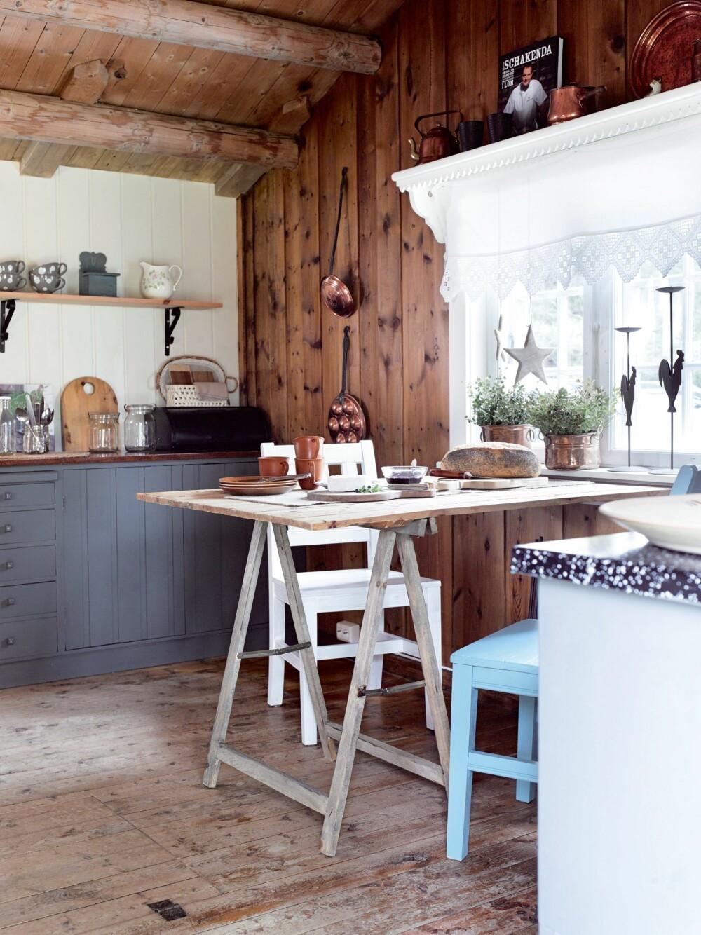GJESTEKJØKKEN I GAMLEHYTTA: En gammel dør funnet i skjulet er blitt til en bordplate. Den er smurt inn med jernvitriol for å stå i stil til det røffe gulvet. Innredningen er snekret på stedet. Hyllen over vinduet og stolene er laget av Sidsels far. Gardin og kobbergjenstander er bruktfunn. Benkeplaten er malt med oljebeis i tjærebrun og satt inn med halvblank trestjernes lakk. En arbeidsbukk fra Biltema er satt inn med jernvitriol for å få en gammel patina som kler bordplaten og gulvet.
