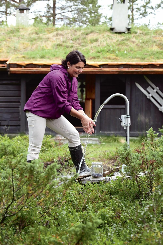 FRISKT VANN: Sidsel Espe henter vann fra vannposten på tunet, som er fra Vasspumper på Biri. Vannet bæres inn til kjøkkenet og en varmtvannsbereder i badehuset.