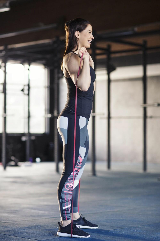 Plasser strikken under hælene og over skuldrene. Stå litt bredere enn hoftebreddes avstand med beina, bøy knærne og kom så dypt ned du klarer mens ryggen holdes nøytral. Press opp igjen til startposisjon.