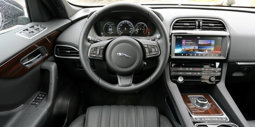 IKKE PREMIUM NOK: Interiøret virker litt for lite gjennomført i forhold til prisen. I nedre del av dørene og midtkonsollen har Jaguar brukt lavprisplast. Skjermen er stor og på norsk. Det er bra.