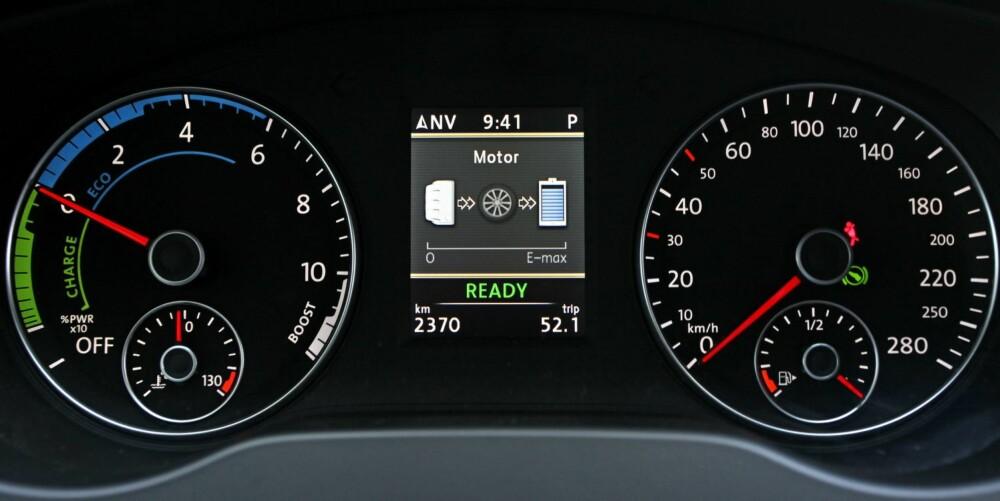 DRIVKREFTER: Både mellom klokkene i dashbordet og på infoskjermen på radioen kan du se kraftflyten i VW Jetta Hybrid. Batteriet lades ved regenerering av rulle- og bremsekraft, og bensinmotoren bidrar til ladingen når batteriet har lite strøm