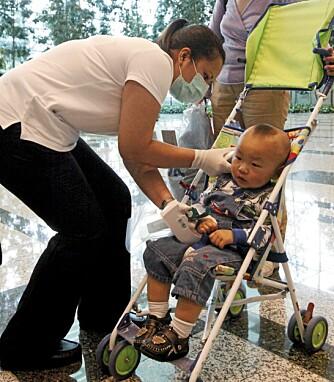 TAR TEMPEN: En helsearbieder måler temperaturen på en liten gutt ved Changi International Airport i Singapore mandag.