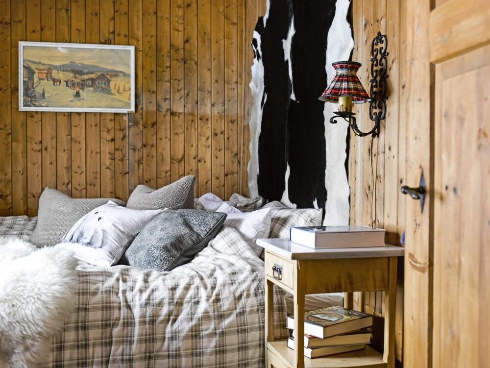 PERSONLIG VEGGPRYD: Skinnet på veggen i soverommet er fra egen okse, som i sin tid tuslet rundt på setra. En påminnelse om gårdslivets nære forhold til dyrene. Tekstiler og skinn kan være fint i stedet for sengegavl når plassen er liten. Sitter man i sengen og leser, er det mykt å lene seg inntil. FOTO: Per Erik Jæger