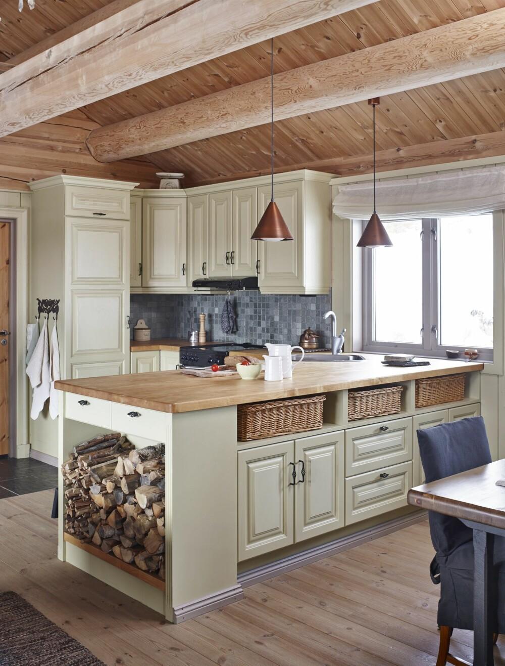 FLOTT KJØKKEN: Kjøkkenet har Kari tegnet selv, men det er Atico som har laget det. Legg merke til kobberlampene over kjøkkenbenken. Kobber går igjen i takrenner, utelamper og altså på kjøkkenet. En vedhylle som en integrert del av kjøkkeninnredningen er både praktisk og dekorativt. FOTO: Sveinung Bråthen