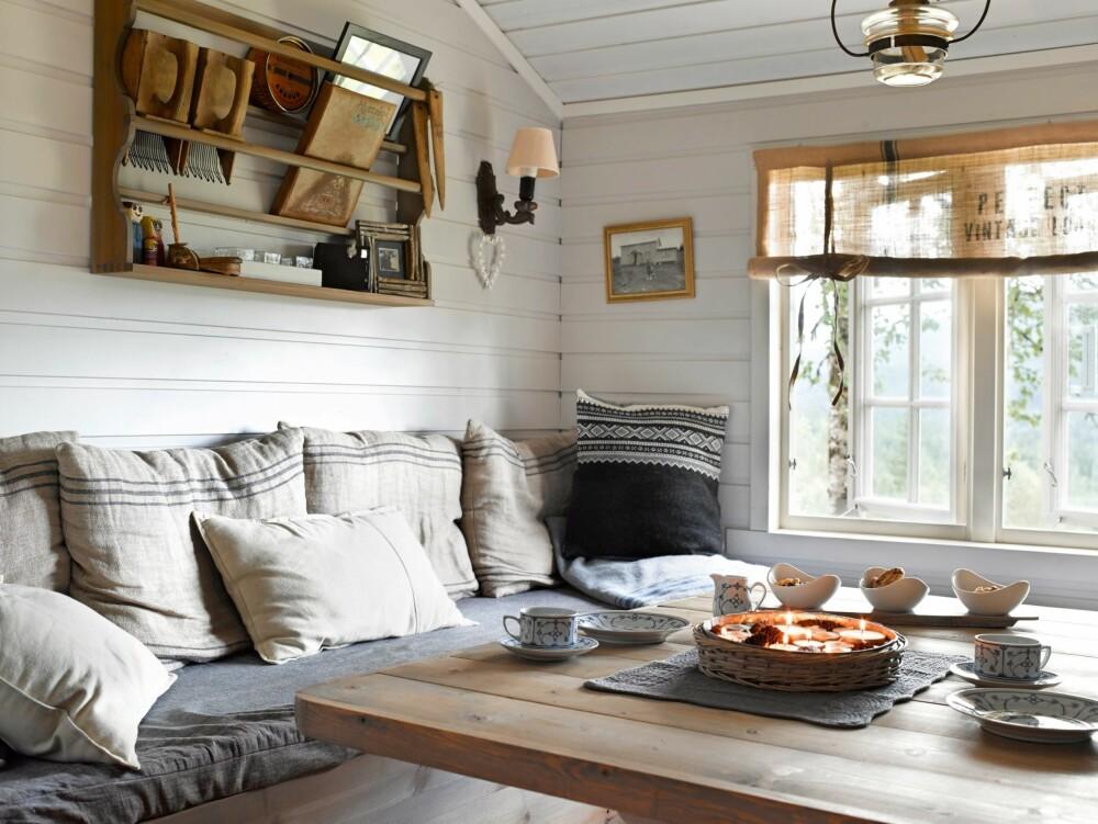 GAMLE SKATTER: Det er mange gamle gjenstander og arvegods i hytta. Anne liker kombinasjonen med nytt og gammelt. Tallerkenhyllen er fra en bruktbutikk. Bestemoren til Anne har sydd putetrekk til noen av putene i sofaen, og hun har selv malt alle flatene.