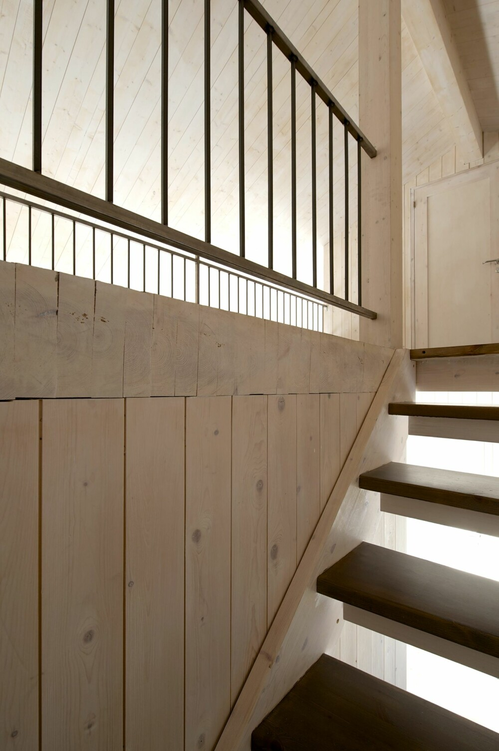 TRAPPEN OPP: I trappegangen ser vi også litt av hvordan bygningen er satt sammen av massive treelementer i vegger, gulv og tak. Både rekkverket og vedvognen i stuen er sveiset av ubehandlet stål hos Tveit Smie på Hundorp.