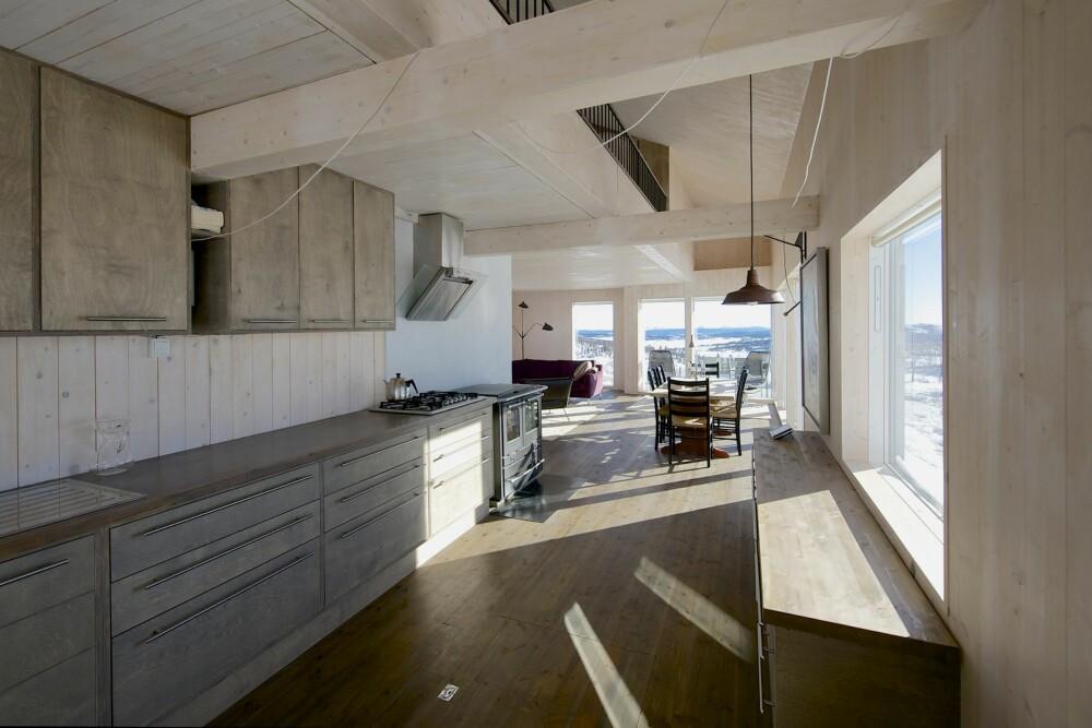 ÅPEN LØSNING: Kjøkkenet, som eieren selv har tegnet, er plassert sentralt i hyttas hovedrom, og slik at skap og hyller tar minimalt med plass. Interiøret er minimalistisk, og dagslyset får flomme inn via den lange vindusrekken. Hemsavdeling er like under mønet og luke til frostfri kjeller i kjøkkengulvet.