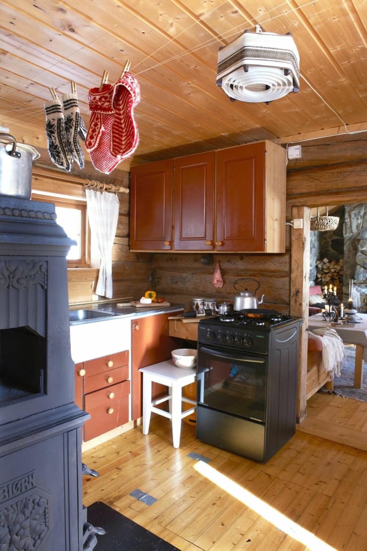 I MIDTEN: Kjøkkenet er plassert midt i hytta, og blir derfor også en naturlig gjennomgangssone mellom soverom og stue. Kjøkkeninnredningen er plassbygget, og fungerer like bra i dag som da det ble satt opp for 30 år siden. Gasskomfyren er blant de få moderne tilskuddene til hytta, den gjør matlagingen litt enklere.