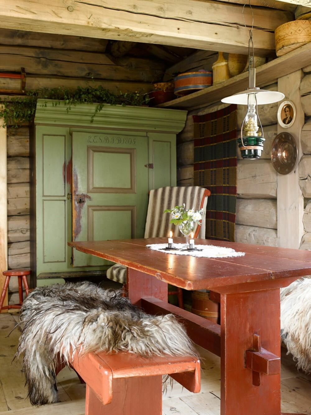 SPISEBORD: Spisekroken i stuen sett fra sofaen. Fargene på møblene som har stått på setra lenge harmonerer fint med gløden fra tømmerveggene. Om kvelden tennes parafinlampen.