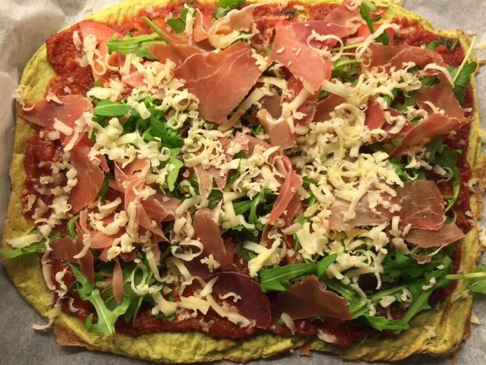 PÅ TOPPEN: Den grønne pizzabunnen fikk selskap avserranoskinke, ruccola, tomat og ost.
