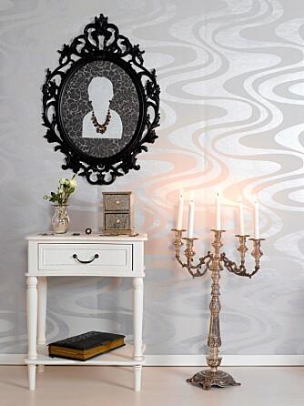 ET SMYKKE: En ornamentramme, «Ung Drill» fra IKEA, er brukt som ramme rundt bestemors arvesmykke. Figuren er klippet ut i «sølvpapp» og limt på et tapet, «Villa Snøringsmoen» fra Sprossa.no. Smykket er festet med små nåler stukket inn fra baksiden. «Sølv»-tapetet på veggen, «Front», kommer fra Borge.