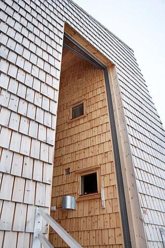 MONUMENTALT: Det som på avstand ser ut som en liten dør i et skur, er i virkeligheten en fem meter høy port.