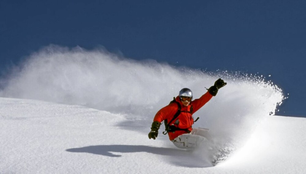 snowboarder is riding fresh powder on a perfect day