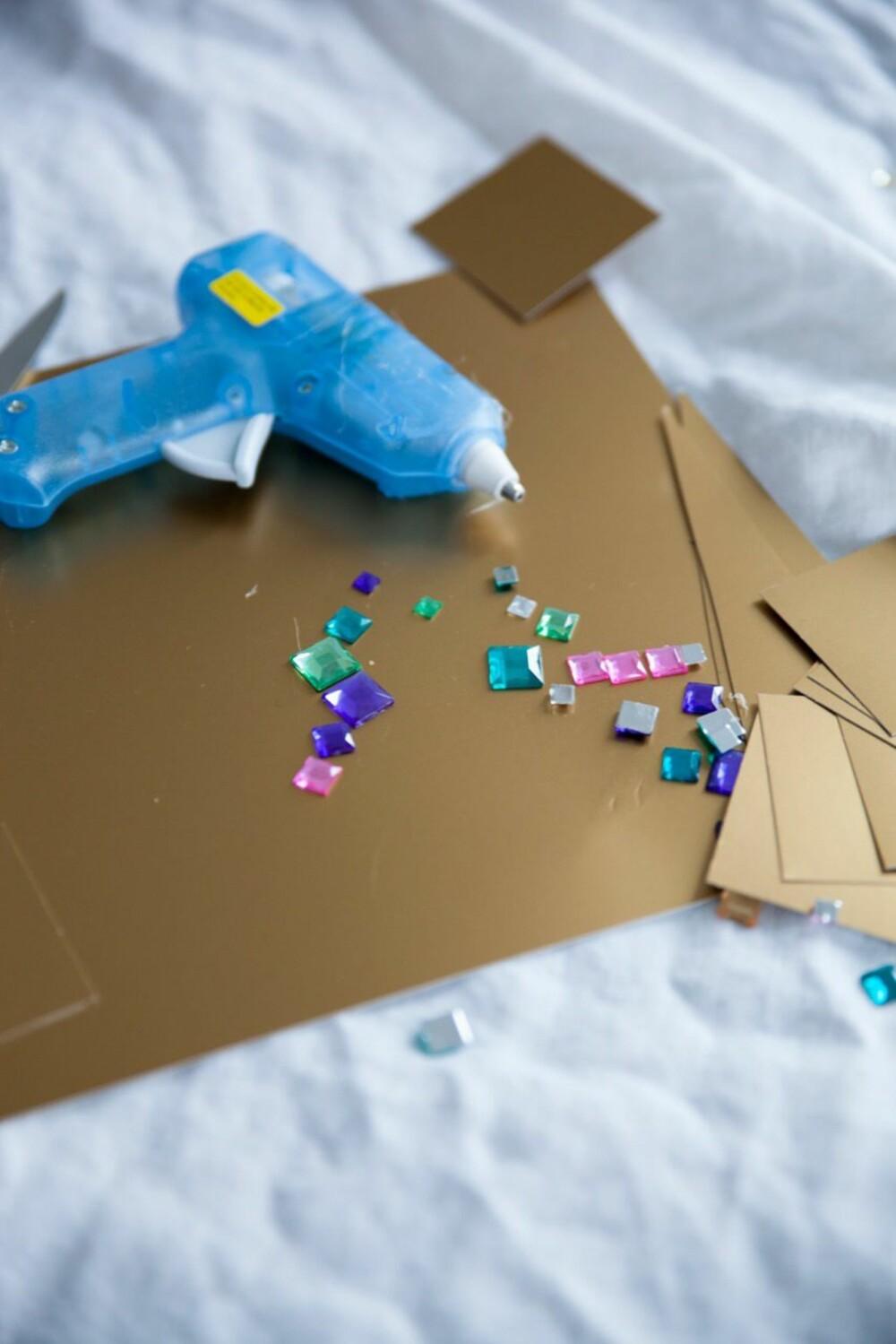TRENGER IKKE MYE: Det er bare litt lim,farget papp, glitter, hyssing og saks som skal til for å lage krone.