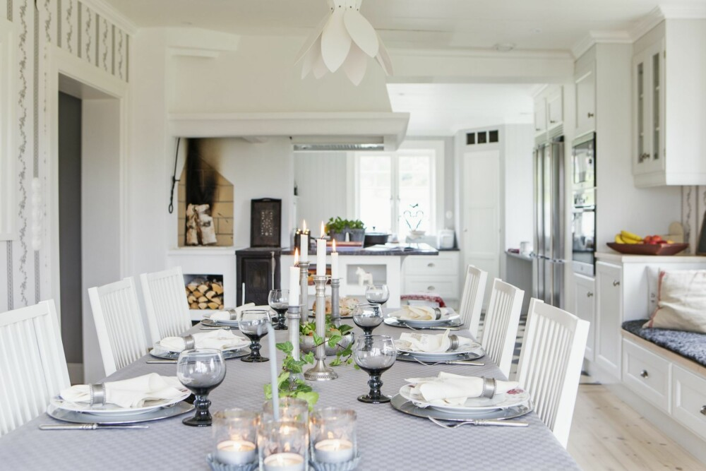 KOSELIG: Tapetet i spisestuedelen heter Karlslund og er fra Borås tapeter. De hvite spisestuestolene understreker den lyse og luftige stilen. Taklampen i metall heter Näckros og er en nytolkning av Carl Larssons papirlampe, fra Huset vid ån.