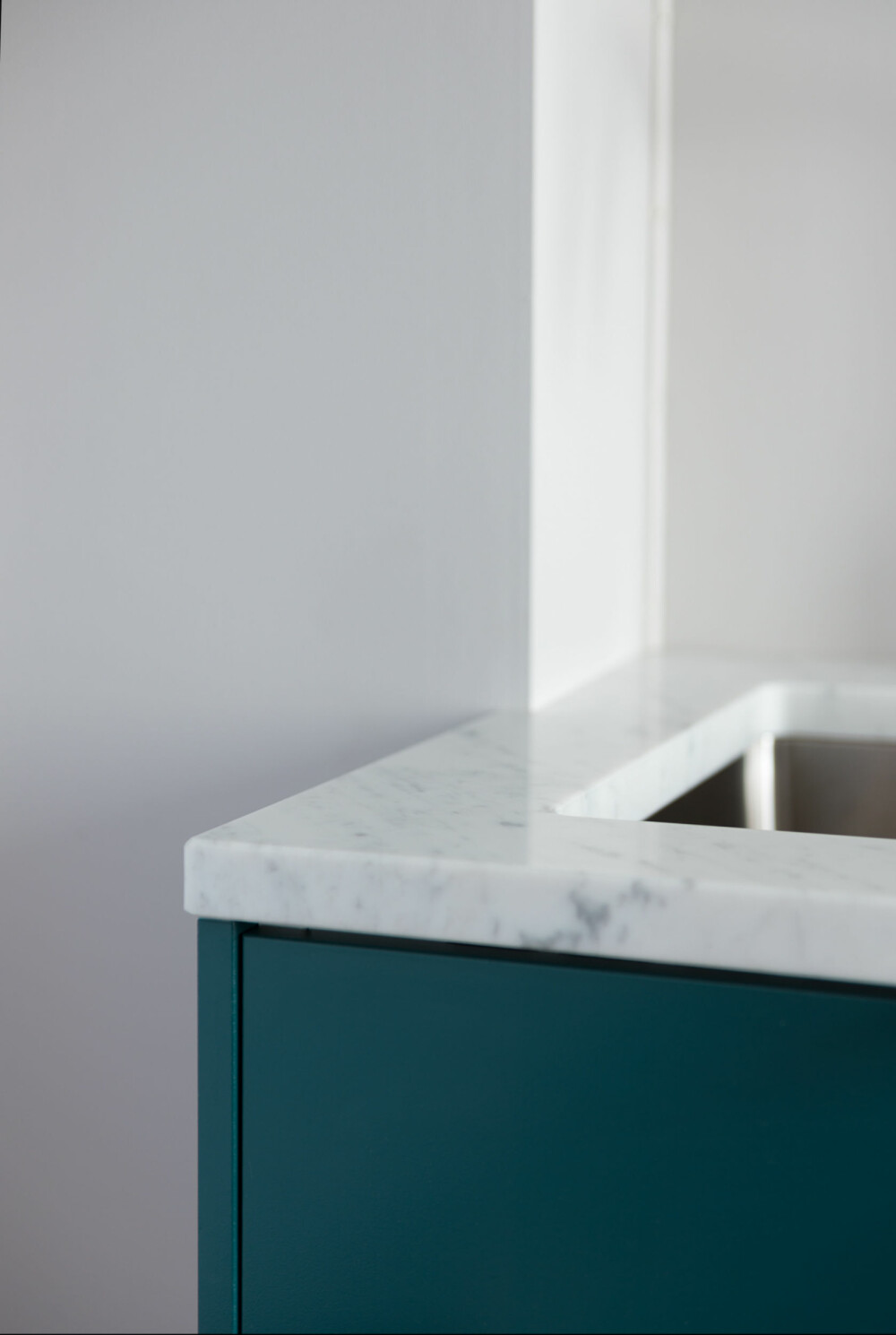 Gjennomført. Marmorplaten er skåret til slik at også enden av kjøkkenbenken kunne kles med en front uten at denne virket påklistret.
