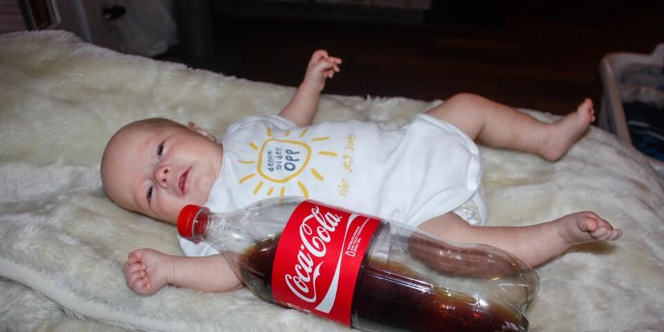 LITEN PRINS: Alle prøver er normale, men Willian vokser ikke som han skal. Her er han fire måneder. En colaflaske på 1,5 liter er lagt ved siden av ham for å vise hvor liten han er. Foto: Privat.
