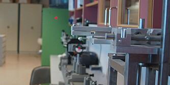 LASERMÅLING: Elevene ved optikerutdanningen har laget et eget måleinstrument for prismatisk effekt. Den røde prikken på veggen er laser. Dersom laserprikken beveger seg for mange millimeter har brillene prismatisk effekt.