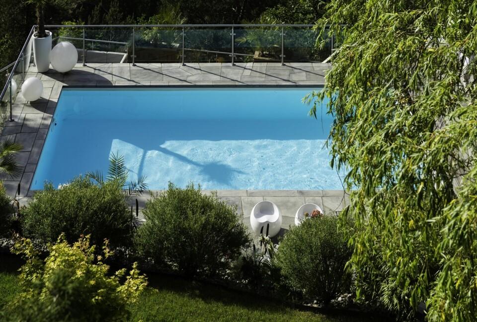 BASSENG I HAGEN: I det stupbratte terrenget har Hanne og Rune Holsted fått plass til et basseng på 32 kvadratmeter, et raust anneks og en rekke uteplasser. FOTO: Niklas Hart.