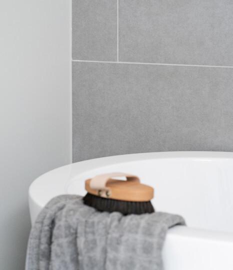 Gulvflisene er trukket opp bak badekaret og den siste veggen er malt med våtromsmaling. Variasjon er vakkert og løsningen gir muligheten for enklere å kunne endre med en annen farge, hvis ønskelig. I tillegg er er maling et rimelig alternativ, sånn at du kan bruke mer av budsjettet på de flisene du ønsker. Foto: Espen Grønli
