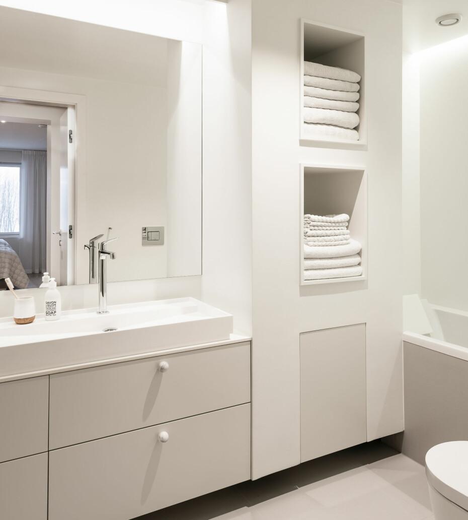 Badet er stramt med rene, hvite flater og skjult belysning. Dusjrommet er lagt til venstre, badekaret til høyre. Innredningen fra HTH med servant fra Hansgrohe og et stort speil er plassert i midten for å strekke siktlinjene ytterligere. Marmorknottene er fra Superfront.