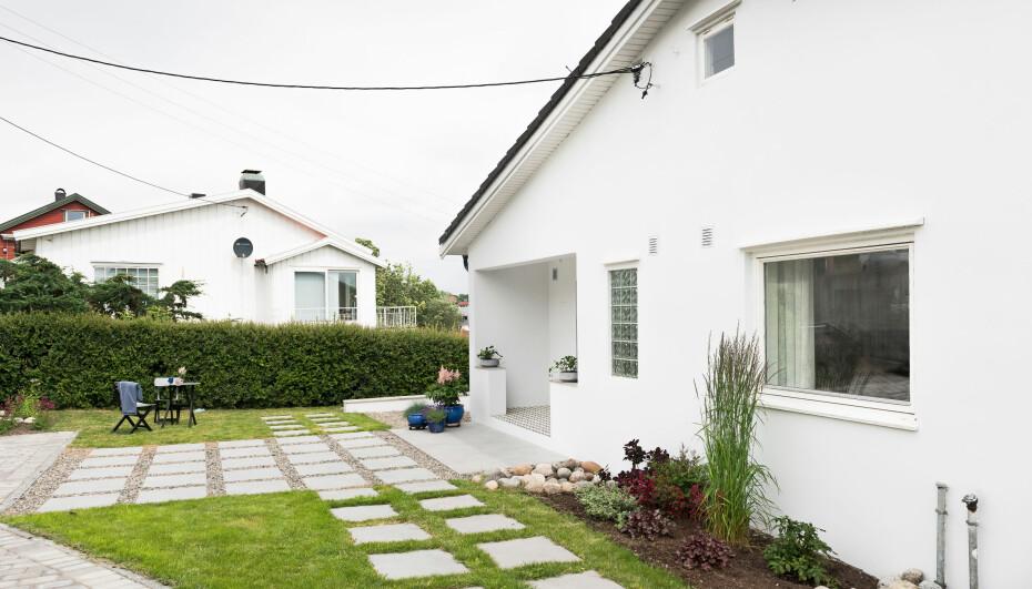FASADEFORANDRING: Det store arealet foran huset er blitt delt inn i soner, som defineres av materialvalget. Hellene er gangareal, mens belegningssteinen til venstre kan benyttes av biler. Balkongmøblene er flyttet ut på gresset.